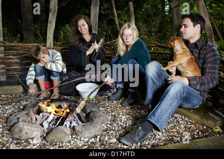 Family relaxing by fire outdoors - Stockfoto