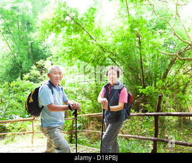 senior couple hiking in the nature with bamboo background - Stock Photo