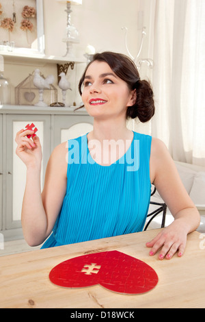 Woman doing heart shaped jigsaw puzzle holding piece - Stockfoto