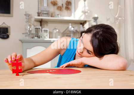 Woman doing heart shaped jigsaw puzzle - Stock Photo