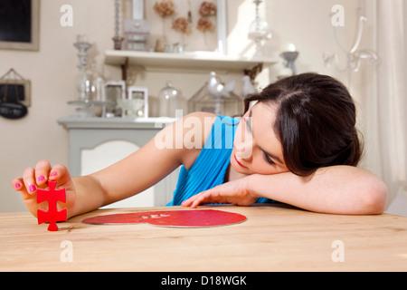 Woman doing heart shaped jigsaw puzzle - Stockfoto