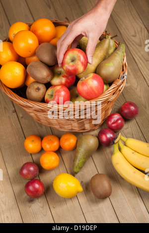 Hand picking up an apple from basket - Stock Photo