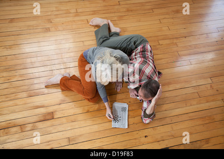 Couple doing crossword on wooden floor - Stock Photo