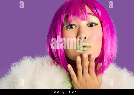 Portrait young funky woman in pink wig blowing kiss over purple background - Stock Photo