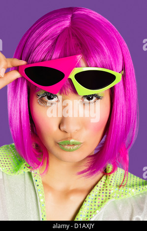 Portrait young funky woman in pink wig puckering lips over purple background - Stock Photo
