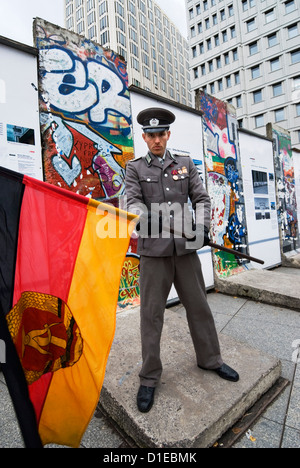 East German guard with former GDR flag in front of remains of the Berlin Wall, Potsdamer Platz, Berlin, Germany, - Stock Photo