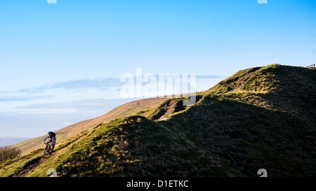 Mountain biker rides down a hilly trail in the Peak District, England, United Kingdom - Stock Photo