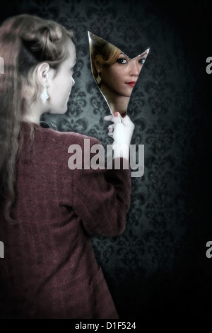 a woman is looking into a broken mirror - Stock Photo