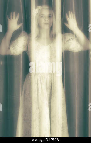 a girl is looking through a curtain - Stock Photo
