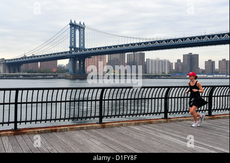 American woman runs under Manhattan Bridge on October 10 2009 in Manhattan New York. - Stock Photo