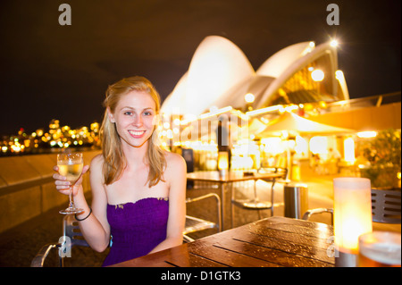 Young woman enjoying Sydney nightlife, having a drink at Opera Bar, Sydney Opera House, Sydney, New South Wales, - Stock Photo