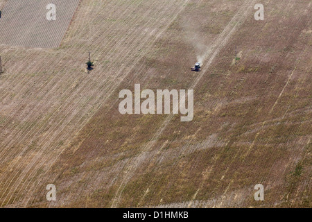 Aerial view tractor plowing agricultural field - Stock Photo