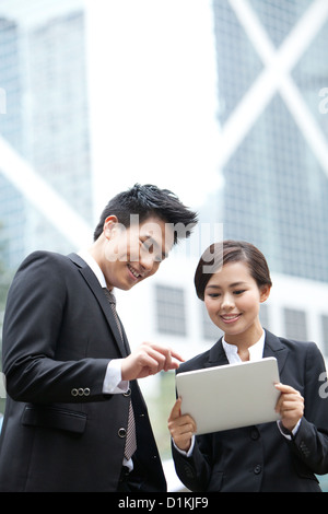 Happy business colleagues using digital tablet together outdoors, Hong Kong - Stock Photo