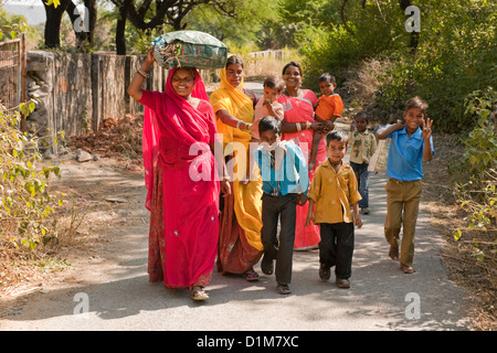 A happy smiling colorful Indian family group of women boys girls and a baby return from shopping on a quiet road - Stock Photo