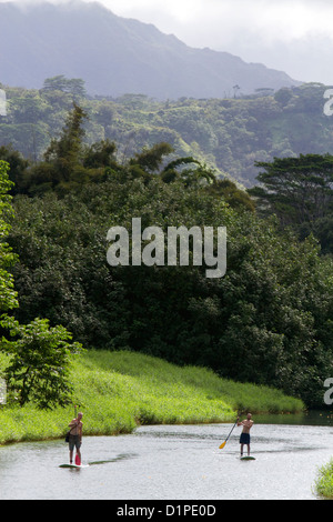 Stand up paddle boarding the Hanalei River on the island of Kauai, Hawaii, USA. - Stock Photo