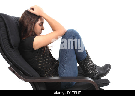 Beautiful girl worried seated on a coach with a white isolated background - Stock Photo