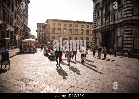 Tourists and locals wander through the Piazza del Duomo in Florence on a lovely summer evening. - Stock Photo