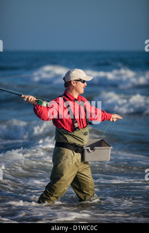 Man fly fishing in the surf of ocean at the beach stock for Surf fly fishing