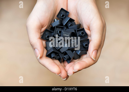 Keyboard keys in woman's hands with a 'Cloud' key in the center, cloud computing service offer concept - Stock Photo