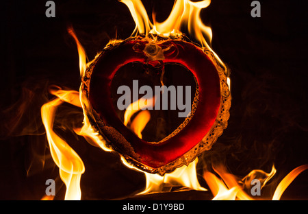 Burning love flaming fire heart with black background - Stock Photo
