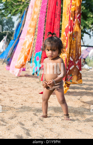 Indian baby girl playing in the sand next to saris on washing line. Andhra Pradesh, India - Stock Photo