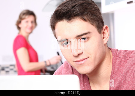 Young male using a laptop, a woman is in the background cooking. - Stock Photo