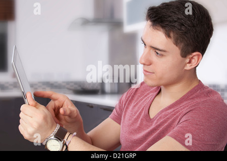 Young man using a digital tablet, looking at the screen or monitor. Situated in a modern kitchen. - Stock Photo