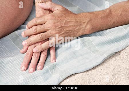 Spain, Mallorca, Senior couple holding hands at beach - Stock Photo