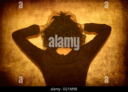 Young woman head in hands - Stock Photo
