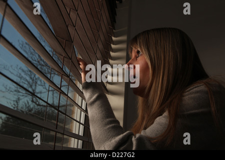 Anxious mature woman peering through window blinds at night. - Stockfoto