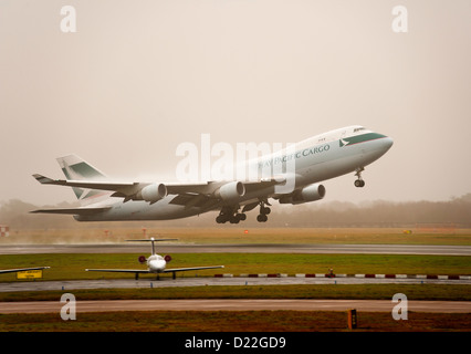 Cathay Pacific Airways Boeing 747-467F (ER) (SCD) Freighter Airliner B-LID Taking Off in Mist at Manchester Airport - Stock Photo