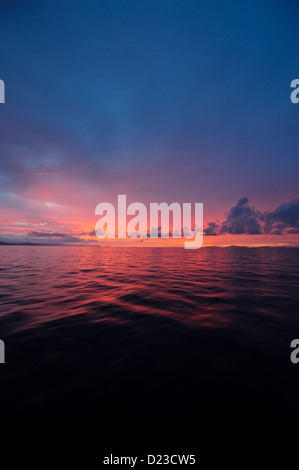 A perfect sunset at sea. Calm waters blue purple red pink light and few clouds after rain giving a romantic atmosphere - Stock Photo