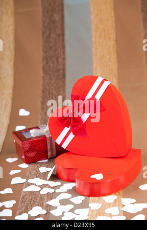 Red box in heart shape on an artistic background macro studio shot - Stock Photo