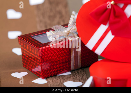Gift box next to Red box in heart shape on an artistic background macro studio shot - Stock Photo