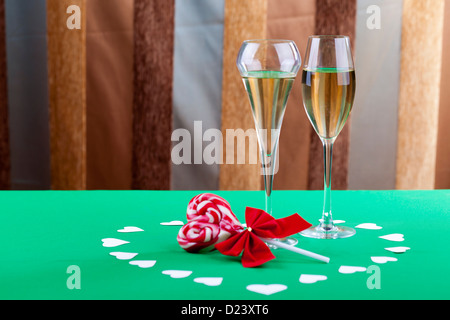 Two glases of champagne next to a heart shape candy on an artistic background - Stockfoto