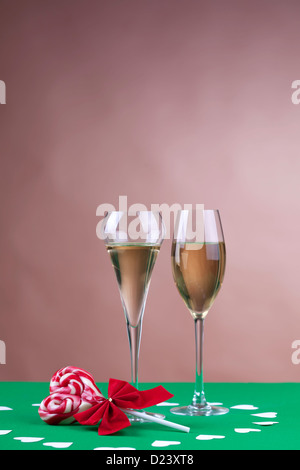 Two glases of champagne next to a heart shape candy on brown background - Stockfoto