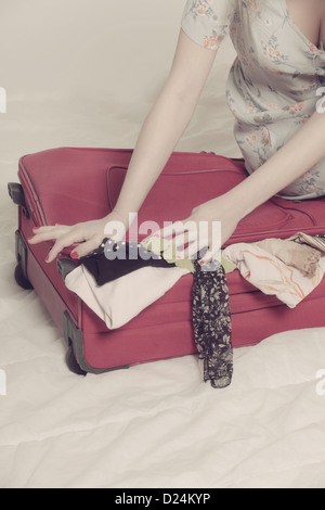 a woman tries to close a suitcase - Stock Photo