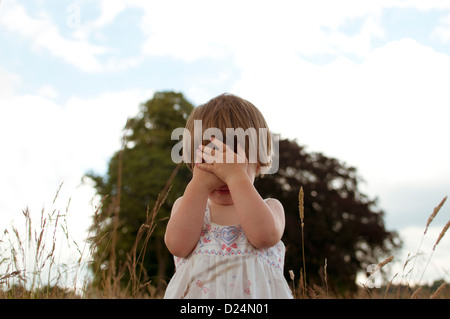 A little girl playing hide and seek outdoors - Stock Photo