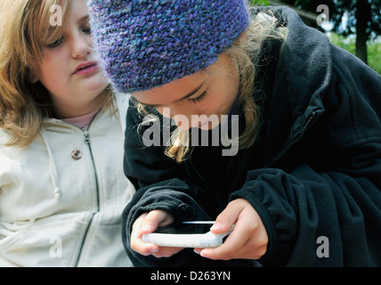 two girls playing on an iphone - Stock Photo