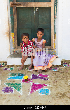 Young Indian village girl and boy sitting on doorstep of their home. Andhra Pradesh, India - Stock Photo
