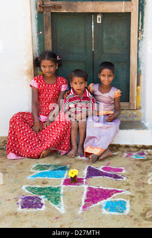 Young Indian village girls and boy sitting on doorstep of their home. Andhra Pradesh, India - Stock Photo