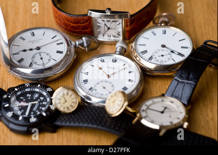 Group of pocket watches and wristwatches, on an oak table top. - Stock Photo