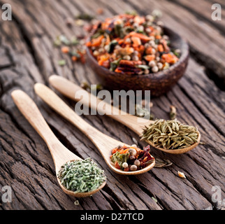 Variety of spices in the spoons on an old wooden table. - Stock Photo