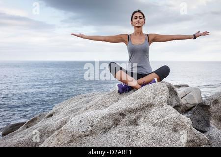 Woman meditating on boulder - Stock Photo