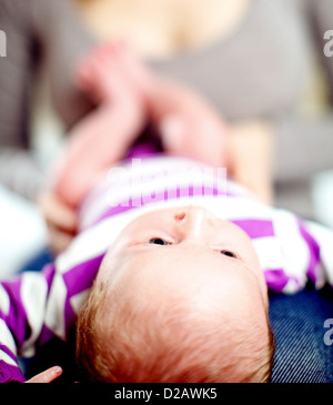 View from the top of the head of a tiny baby lying on its back on its mothers lap - Stockfoto