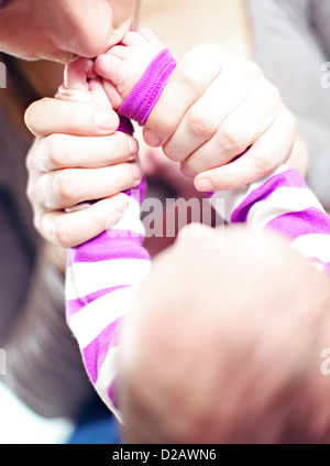 Overhead cropped view of a loving young mother kissing her baby's hands - Stockfoto