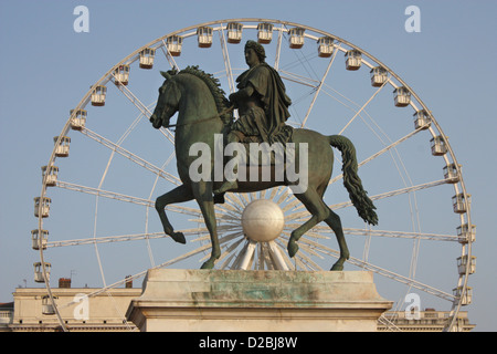 Equestrian statue of Louis XIV in front of the big wheel, Place Bellecour, Lyon, France - Stock Photo