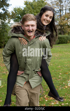 Man carrying girlfriend in park - Stock Photo