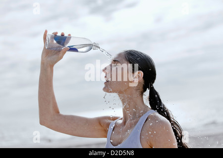 Runner pouring water on herself - Stock Photo