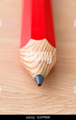 Close up detail of the lead of a red pencil on a wooden background - Stock Photo